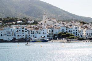 Bahía de Cadaqués con el pueblo blanco de fondo y con un barco atracado en la playa
