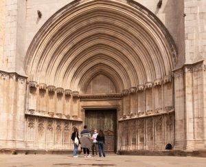 Portal de acceso a la Catedral de Girona con grandes arcos y un grupo de turistas en un tour de girona