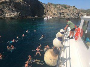 Grupo del tour en barco bañándose en mar